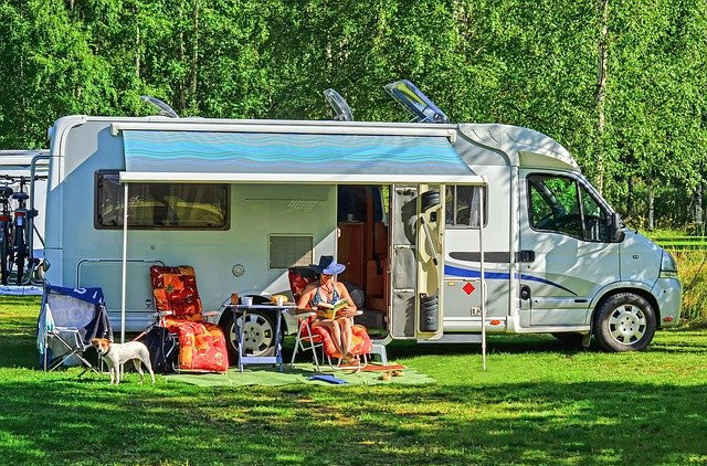Woman sitting in sun outside parked RV